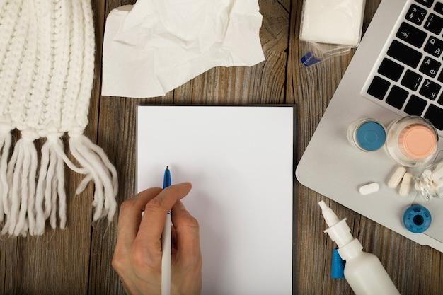 Folha de papel em branco com mão feminina. cachecol de inverno, medicação, laptop em uma superfície de madeira. vista do topo