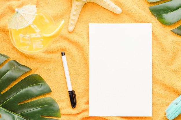 Folha de papel em branco com objetos de praia na luz de fundo