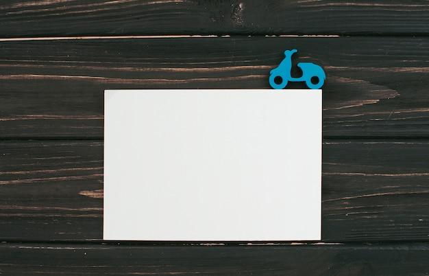 Folha de papel em branco com pequena scooter na mesa