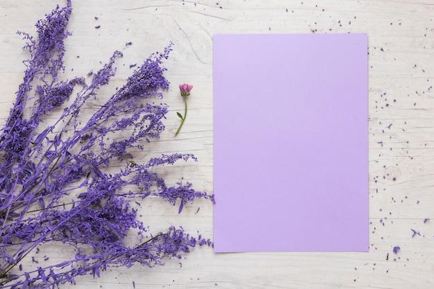 Folha de papel em branco com ramos de flores na mesa