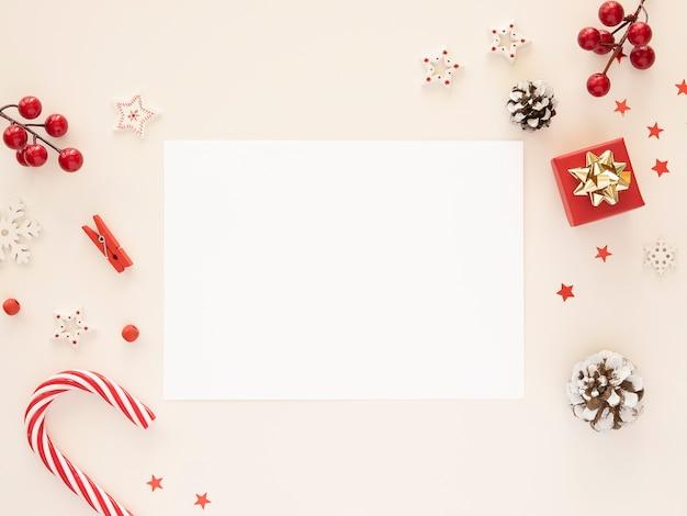 Folha de papel em branco de maquete de carta de natal com decorações de natal em fundo branco