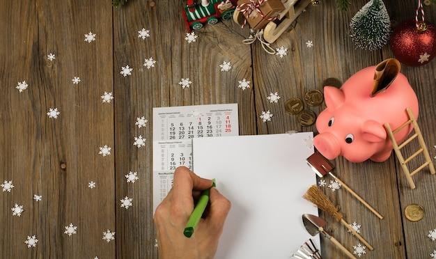 Folha de papel em branco e cofrinho rosa com um fundo de ano novo