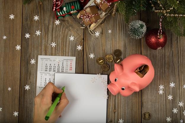 Folha de papel em branco e cofrinho rosa em um fundo de ano novo. vista superior