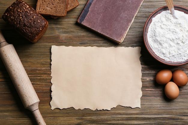 Folha de papel em branco e ingredientes para cozinhar pão em fundo de madeira