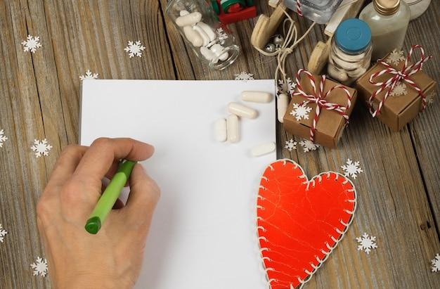 Folha de papel em branco e mão humana produtos farmacêuticos no fundo de ano novo vista superior
