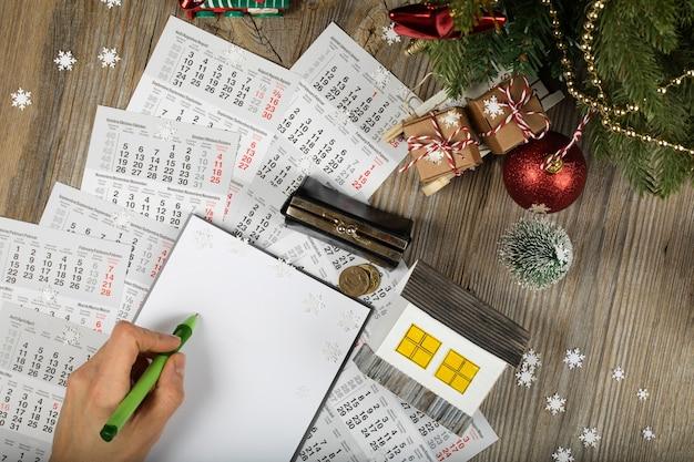 Folha de papel em branco e uma pequena casa de papel com moedas no fundo de ano novo. vista superior
