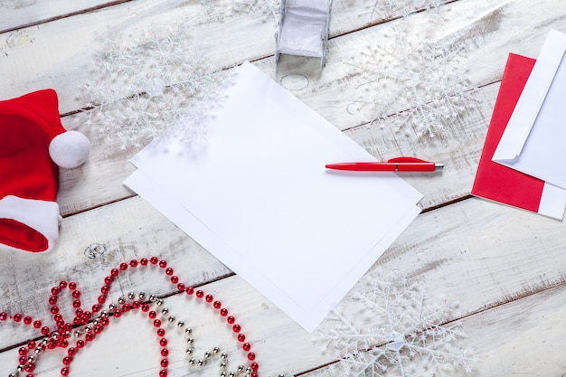 Folha de papel em branco na mesa de madeira com uma caneta e decorações de natal.