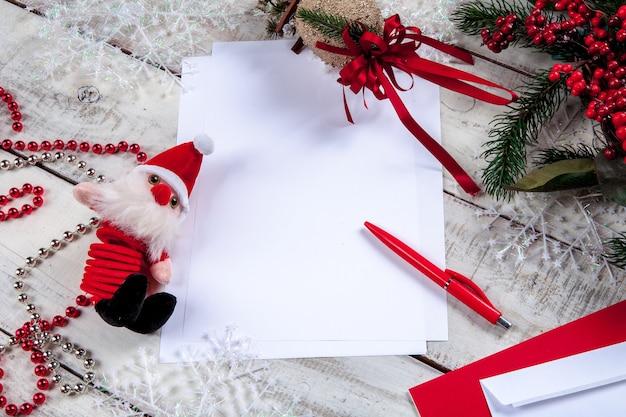 Folha de papel em branco na mesa de madeira com uma caneta e o papai noel.