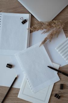 Folha de papel em branco na mesa. espaço de trabalho da mesa do escritório em casa do artista com laptop, lápis, grama dos pampas.
