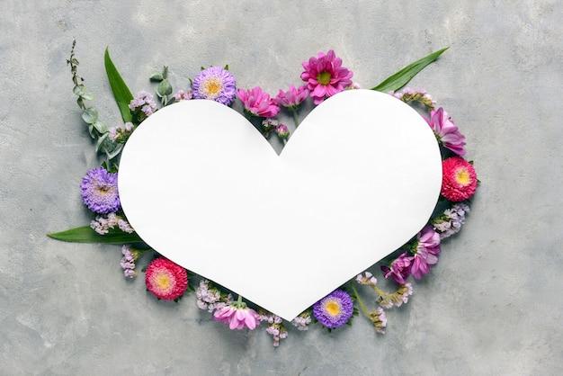 Folha de papel em forma de coração com lindas flores em fundo cinza
