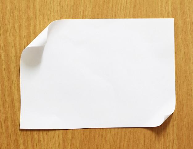 Folha de papel em fundo de madeira