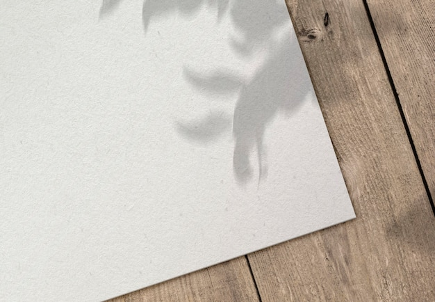 Folha de papel em superfície de madeira com sombra