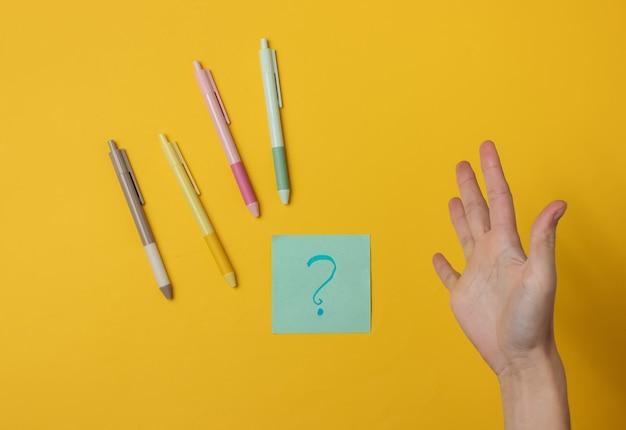 Folha de papel feminina surpresa com um ponto de interrogação e canetas