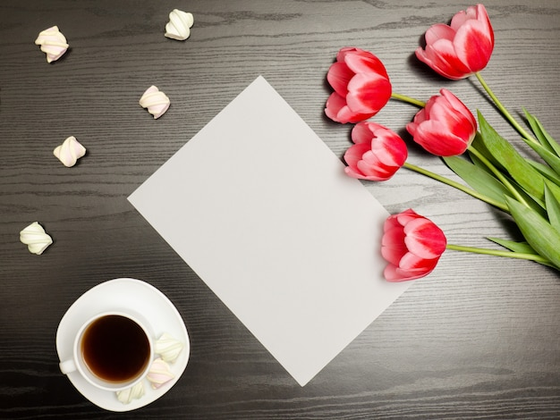 Folha de papel limpa, tulipas cor de rosa e uma caneca de café. mesa preta. vista do topo