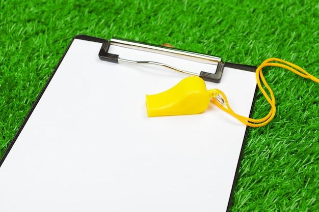 Folha de papel na área de transferência na grama