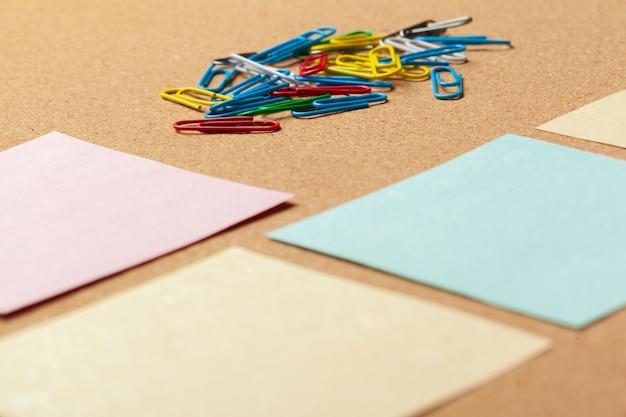 Folha de papel para anotações e clipes de papel no fundo do quadro de avisos