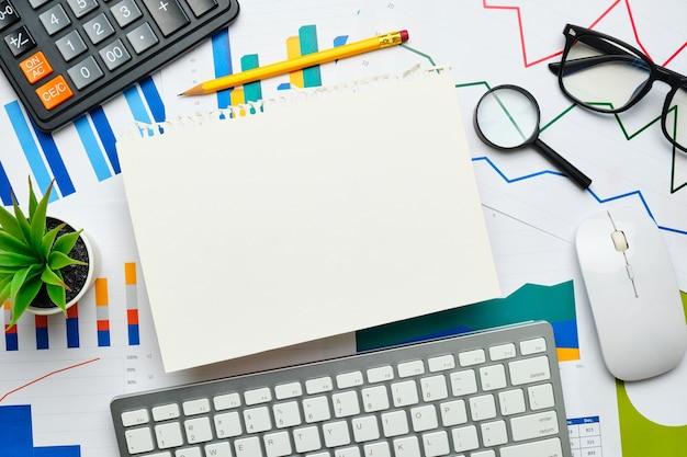 Folha de papel rasgada em gráficos e relatórios de negócios.