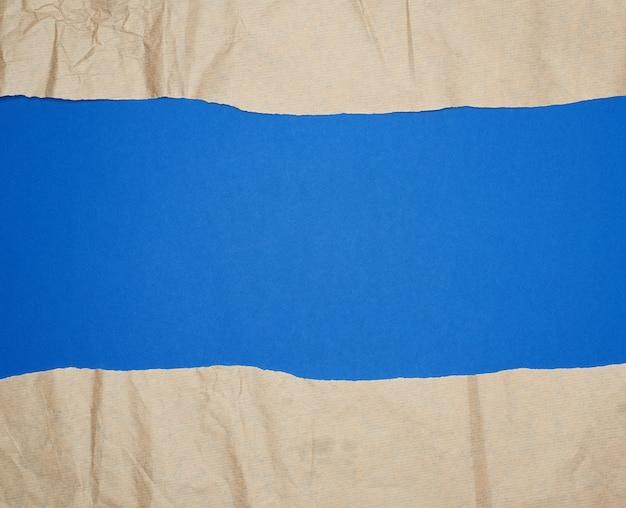 Folha de papel rasgada marrom sobre um fundo azul, quadro completo