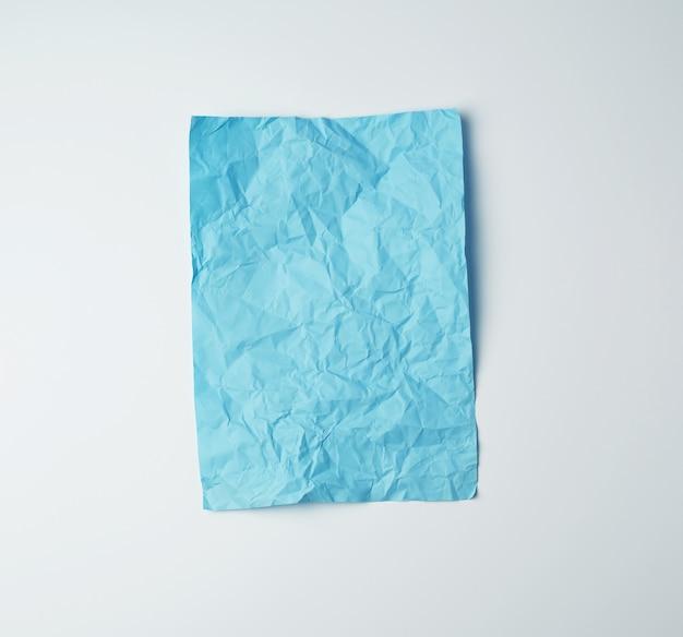 Folha de papel retangular azul amassada vazia em uma superfície branca