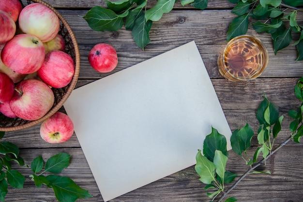 Folha de papel, suco de maçã e maçãs vermelhas