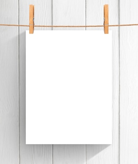 Folha de papel vazia que pendura na corda sobre o fundo de madeira. zombe para o seu projeto com espaço de cópia