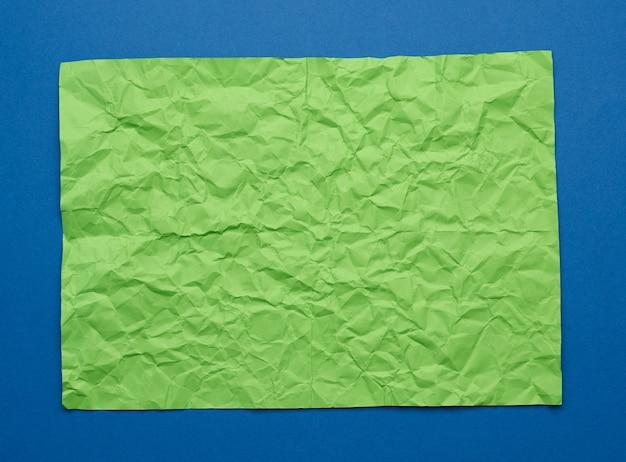 Folha de papel verde amassada em branco sobre fundo azul