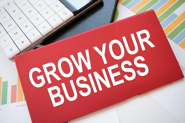Folha de papel vermelha com o texto amplie seus negócios, calculadora e caneta na área de trabalho. conceito de negócios