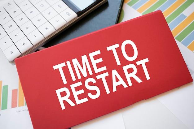 Folha de papel vermelha com o texto hora de reiniciar, calculadora e caneta na área de trabalho. conceito de negócios