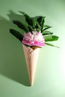 Folha de peônia em um cone de waffle. conceito de verão.