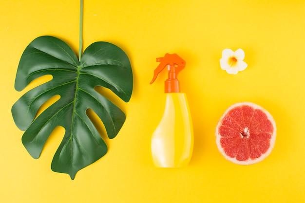 Folha de planta tropical verde perto de garrafa de spray e frutas