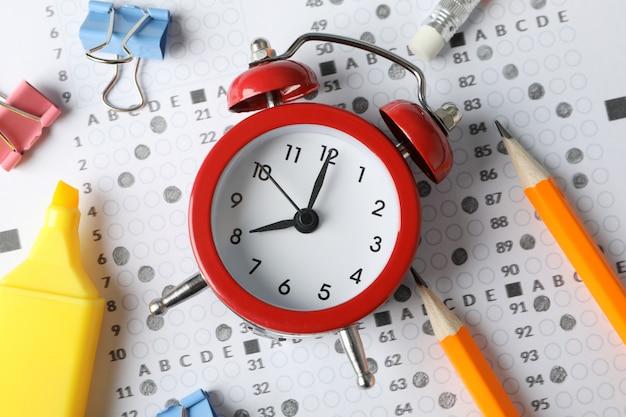 Folha de pontuação do teste, despertador e artigos de papelaria, close-up