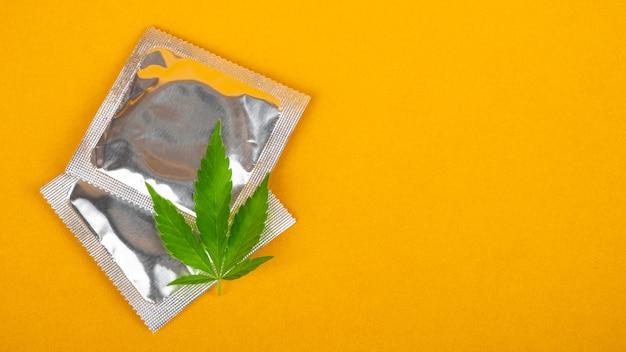 Folha de preservativo e cannabis com espaço de cópia em fundo amarelo, maquete de drogas sexuais.