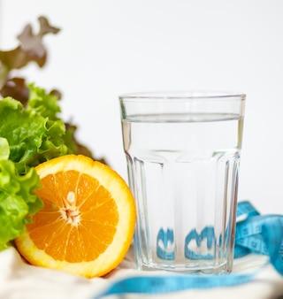 Folha de salade. laranja, copo de água e fita métrica azul em fundo branco, estilo de vida saudável e conceito de água potável