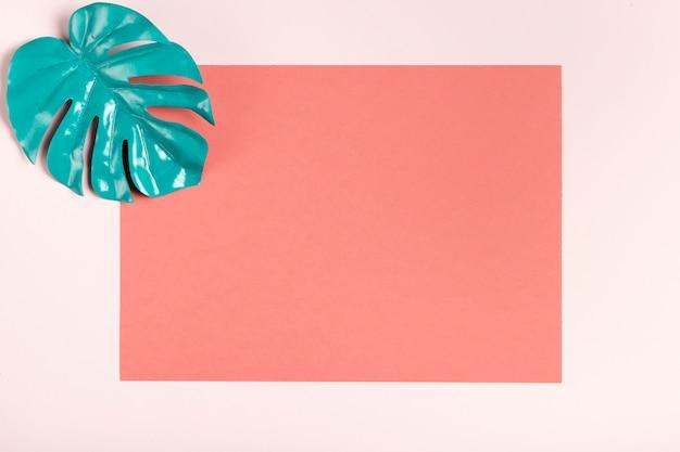 Folha de turquesa na maquete de fundo rosa