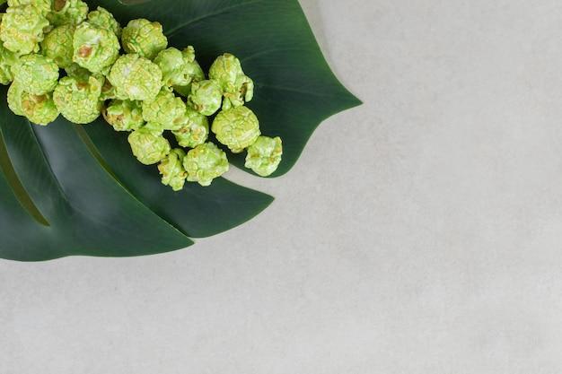 Folha decorativa debaixo de uma pequena porção de pipoca cristalizada na mesa de mármore.