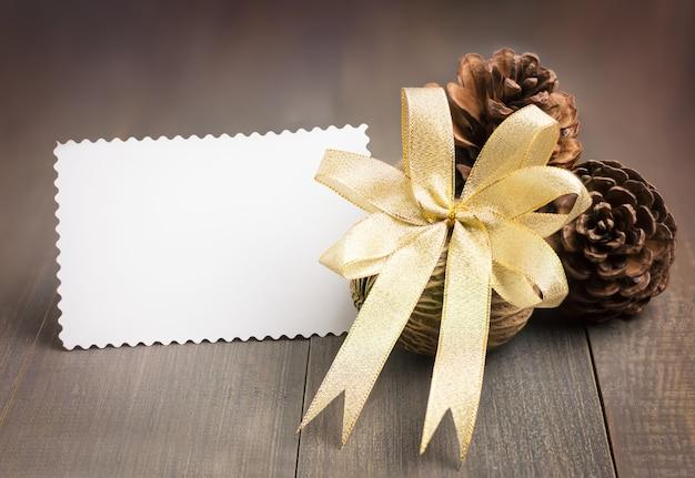 Folha do cartão do livro branco, fita dourada, cones do pinho, semente do othalanga em de madeira marrom.