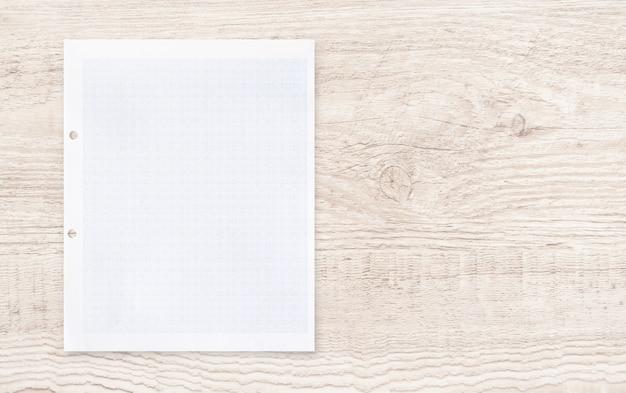 Folha do livro branco com teste padrão da linha de grade na madeira.