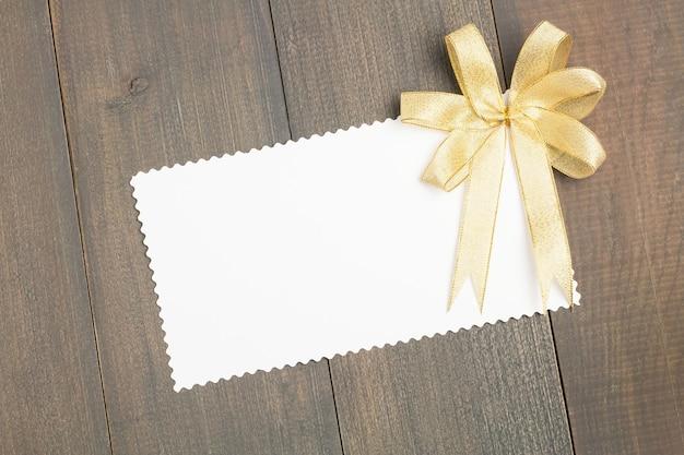 Folha do papel vazio com a fita dourada no fundo de madeira do assoalho do marrom escuro.
