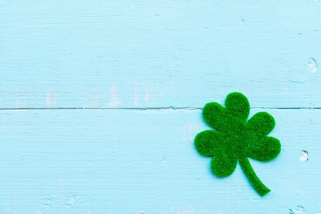 Folha do trevo do papel verde na textura de madeira branca e azul pastel do fundo da tabela.
