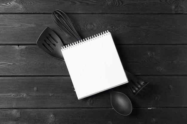 Folha em branco de bloco de notas aberto e utensílios de cozinha na mesa com toalha de mesa, copie o espaço