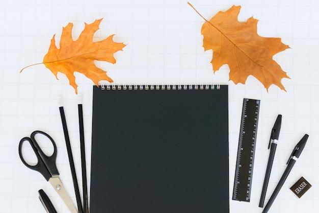 Folha em branco de papel de caderno preto e artigos de papelaria em um fundo branco quadriculado