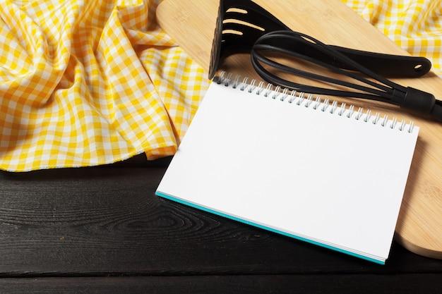 Folha em branco do bloco de notas aberto e utensílios de cozinha na mesa com toalha de mesa, cópia espaço