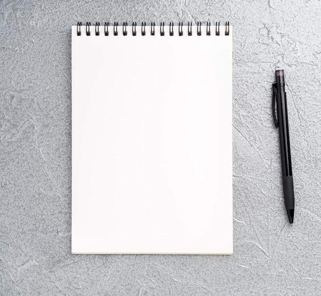 Folha em branco do caderno com uma espiral em um background metálico prateado cinza texturizado neutro