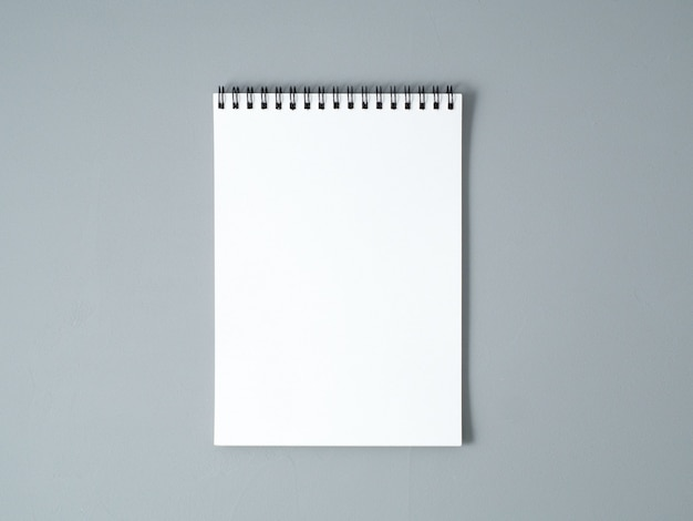 Folha em branco do caderno com uma espiral em um fundo texturizado cinzento neutro
