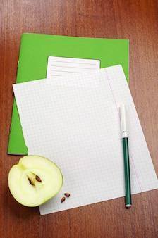 Folha em branco do caderno escolar, fatia de maçã e canetas hidrográficas na mesa