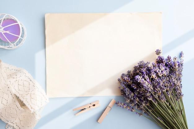 Folha em branco em cima da mesa lavanda, vela, laço