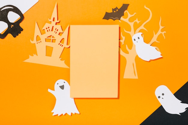 Folha em branco rodeada por decorações de halloween feitas de papel