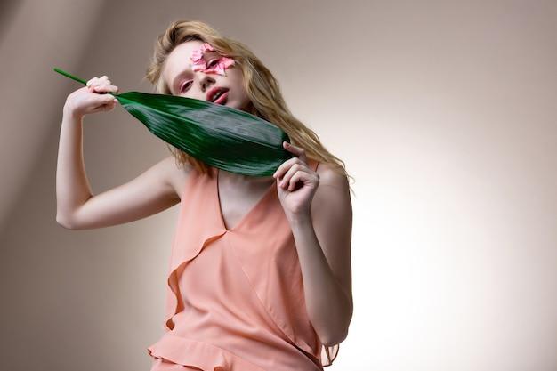 Folha nas mãos. modelo loira usando um vestido elegante e macio posando com flores no rosto e folhas nas mãos