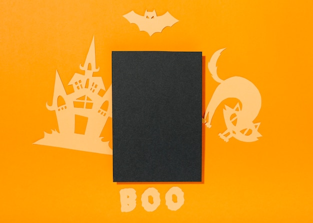 Folha preta com decorações de papel de halloween e boo inscrição