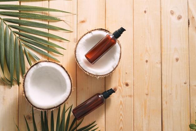 Folha tropical, cosméticos e coco em uma mesa de madeira. vista do topo. meios para cabelo, corpo, pele. flatlay